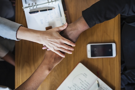 Diverse business team stacking hands